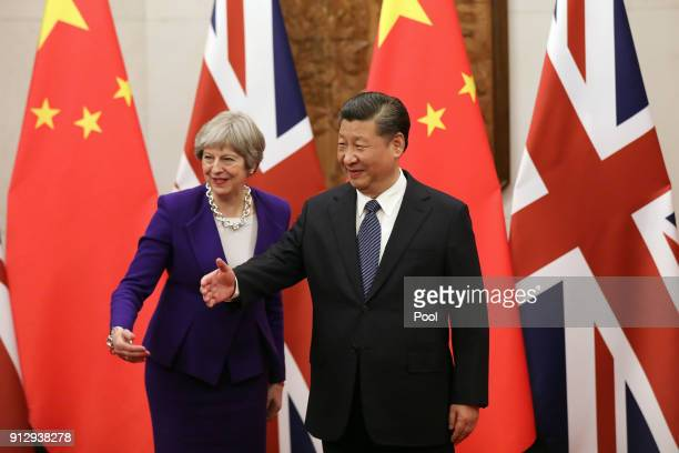 British Prime Minister Theresa May and Chinese President Xi Jinping gesture ahead of a meeting at Mr Jinping's official Diaoyutai State Guesthouse on...
