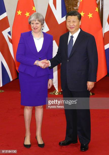 British Prime Minister Theresa May and Chinese President Xi Jinping shake hands before their talks at the Diaoyutai state guesthouse in Beijing on...