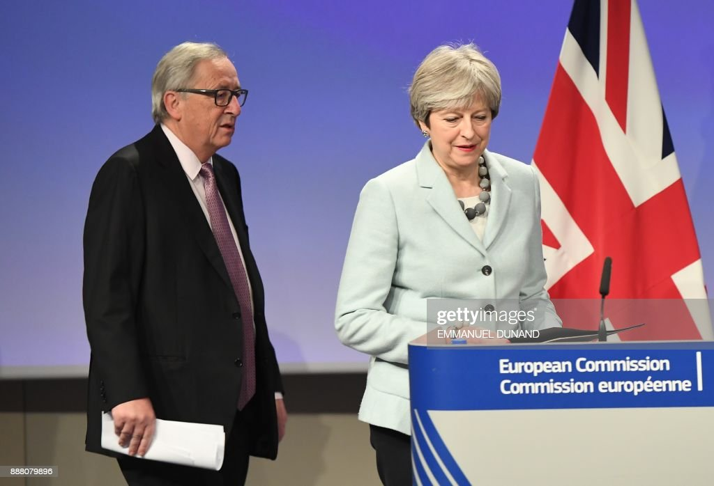 British Prime Minister Theresa May (R) and European Commission President Jean-Claude Juncker arrive to address a press conference at the European Commission in Brussels on December 8, 2017. Britain and the EU reached a historic deal on December 8 on the terms of the Brexit divorce after the British Prime Minister rushed to Brussels for early morning talks. /