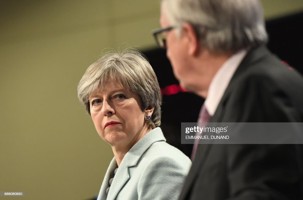 TOPSHOT - British Prime Minister Theresa May (L) and European Commission President Jean-Claude Juncker address a press conference at the European Commission in Brussels on December 8, 2017. Britain and the EU reached a historic deal on December 8 on the terms of the Brexit divorce after the British Prime Minister rushed to Brussels for early morning talks. /