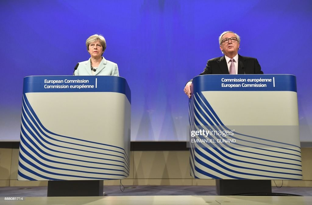 British Prime Minister Theresa May (L) and European Commission President Jean-Claude Juncker address a press conference at the European Commission in Brussels on December 8, 2017. Britain and the EU reached a historic deal on December 8 on the terms of the Brexit divorce after the British Prime Minister rushed to Brussels for early morning talks. /