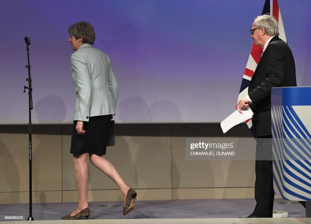 British Prime Minister Theresa May (L) and European Commission President Jean-Claude Juncker leave after addressing a press conference at the European Commission in Brussels on December 8, 2017. Britain and the EU reached a historic deal on December 8 on the terms of the Brexit divorce after the British Prime Minister rushed to Brussels for early morning talks. /
