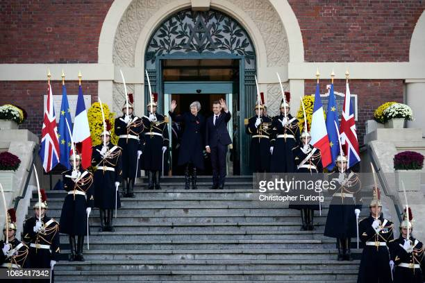 British Prime Minister Theresa May and French President Emmanuel Macron wave as they arrive on the steps of Albert Town Hall for a meeting in the...