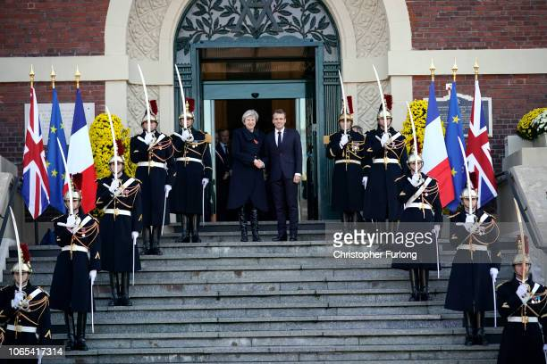 British Prime Minister Theresa May and French President Emmanuel Macron shake hands as they arrive on the steps of Albert Town Hall for a meeting in...