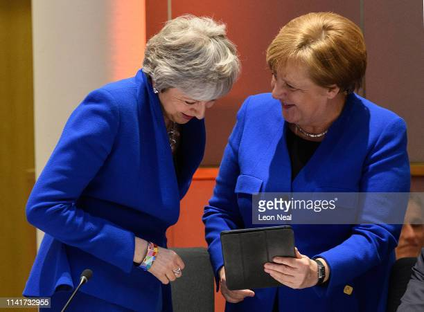 British Prime Minister Theresa May and German Chancellor Angela Merkel share a joke at a round table meeting on April 10 2019 in Brussels...