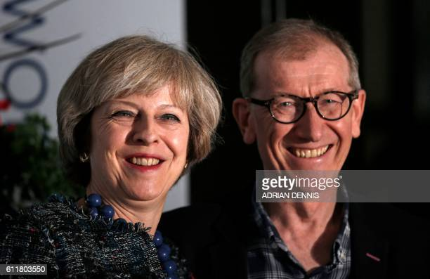 British Prime Minister Theresa May and her husband Philip John May pose for a photograph as they arrive at a hotel close to the International...