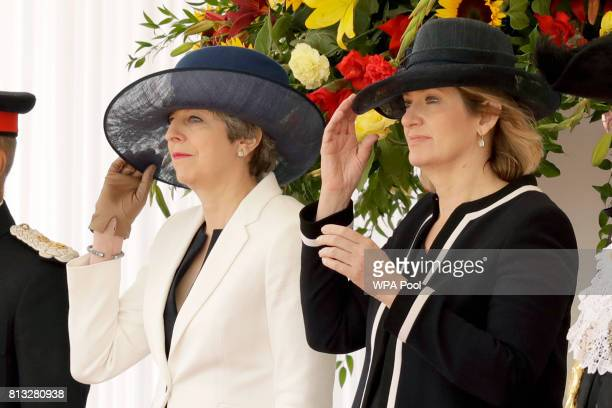 British Prime Minister Theresa May and Home Secretary Amber Rudd hold onto their hats on a windy day at the end of a Ceremonial Welcome for Spain's...
