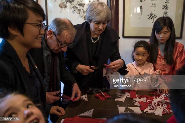 British Prime Minister Theresa May and husband Philip May join schoolchildren in the Yu Yuan Temple Gardens grounds on February 02 2018 in Shanghai...