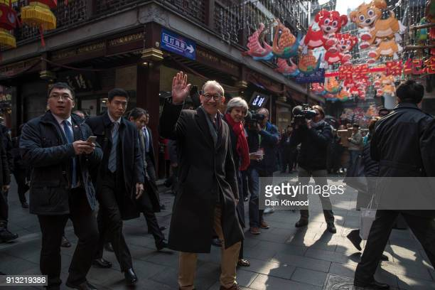 British Prime Minister Theresa May and husband Philip May wave to members of the public as they walk through a market after visiting the Yu Yuan...