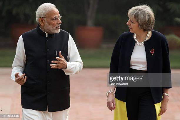 British Prime Minister Theresa May and Indian Prime Minister Narendra Modi walk through the gardens of Hyderabad House on November 7 2016 in New...