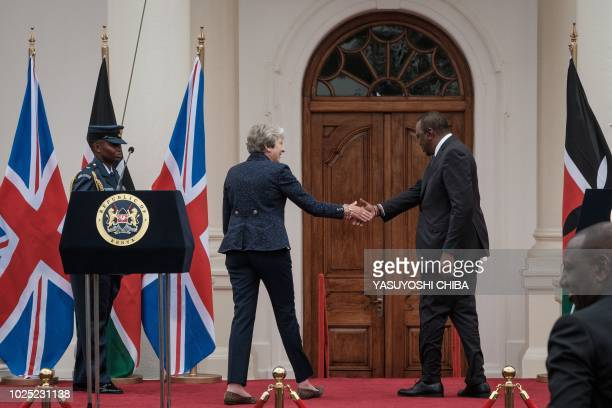 British Prime Minister Theresa May and Kenyan President Uhuru Kenyatta reach out to shake hands after addressing a joint press conference at the...