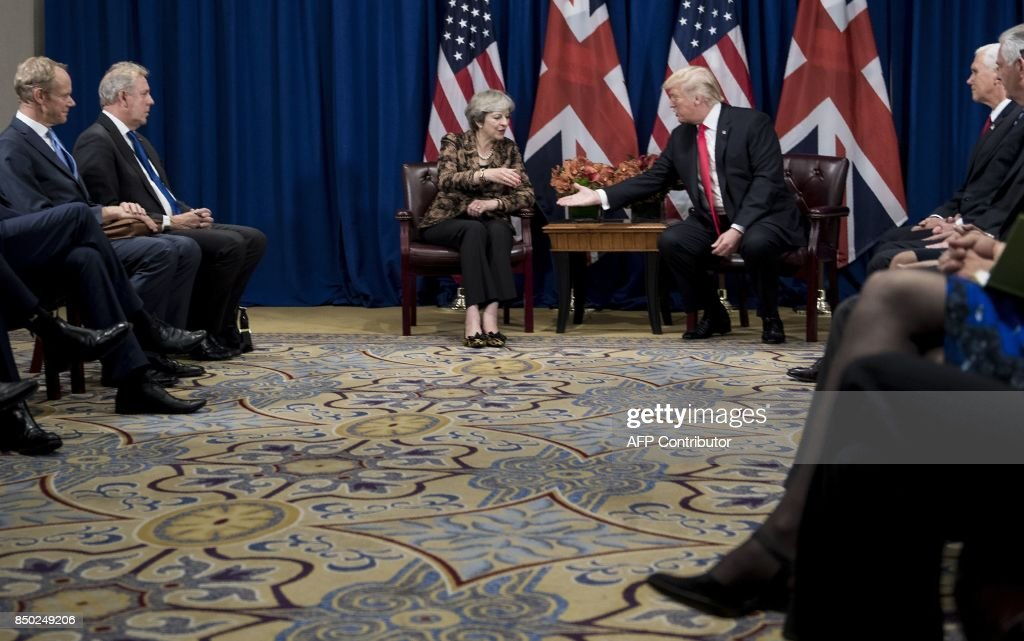 British Prime Minister Theresa May and US President Donald Trump (C) shake hands during a meeting at the Palace Hotel in New York, on the sidelines of the 72nd United Nations General Assembly, on September 20, 2017. / AFP PHOTO / Brendan Smialowski