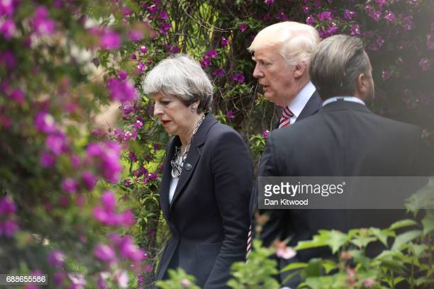 British Prime Minister Theresa May and US President Donald Trump walk together in the grounds of the San Domenico Palace Hotel as they attend a...