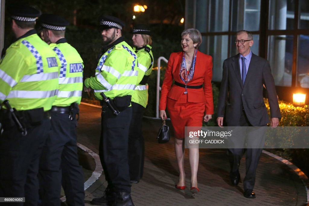 TOPSHOT - British Prime Minister Theresa May (2nd R) arrives with her husband Philip (R) at the count centre in Maidenhead early in the morning of June 9, 2017, hours after the polls closed in Britain's general election. Prime Minister Theresa May is poised to win Britain's snap election but lose her parliamentary majority, a shock exit poll suggested on June 8, in what would be a major blow for her leadership as Brexit talks loom. The Conservatives were set to win 314 seats, followed by Labour on 266, the Scottish National Party on 34 and the Liberal Democrats on 14, the poll for the BBC, Sky and ITV showed. / AFP PHOTO / Geoff CADDICK