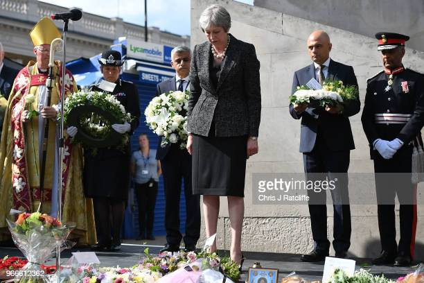 British Prime Minister Theresa May bows her head and lays flowers after the minute's silence at the corner of London Bridge on the first anniversary...