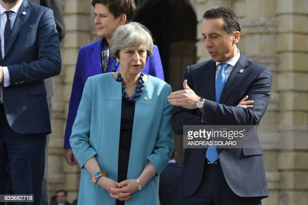 British Prime Minister Theresa May chats with Federal Chancellor of Austria Christian Kern before a family picture during an European Union summit on...