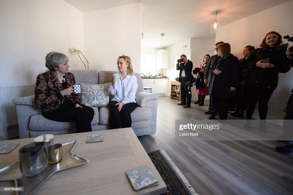 British Prime Minister Theresa May (L) chats with first-time buyer Laura Paine (C) as reporters, security and Downing Street staff look on, during a visit to new housing development Montague Park on January 3, 2018 in Wokingham, England. The Government has today claimed that 16,000 first-time buyers have benefited from changes to the stamp duty rules.