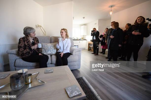 British Prime Minister Theresa May chats with firsttime buyer Laura Paine as reporters security and Downing Street staff look on during a visit to...