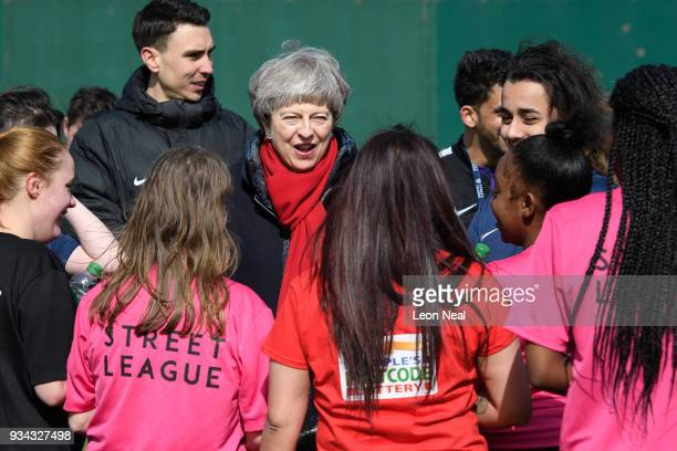 British Prime Minister Theresa May chats with young people at the 'Street League at People Plus' employment charity on March 19 2018 in Birmingham...