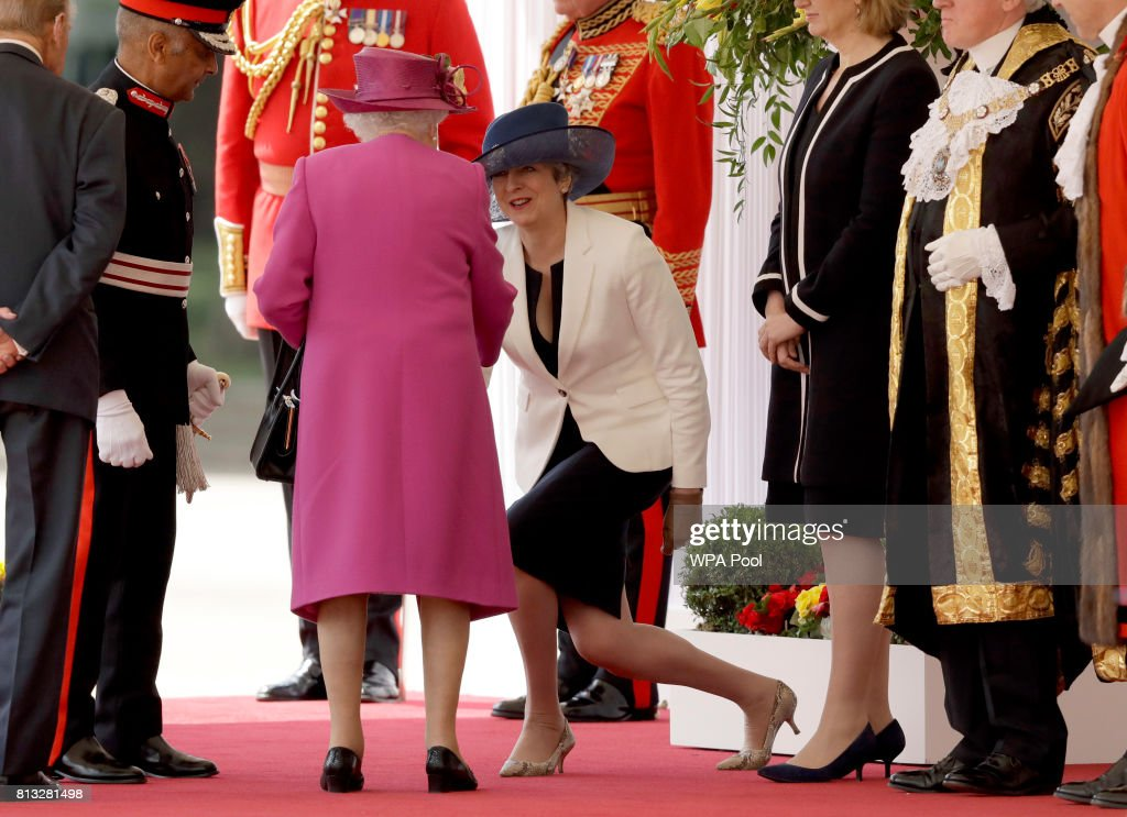 British Prime Minister Theresa May curtsies as Britain's Queen Elizabeth II arrives at a Ceremonial Welcome for Spain's King Felipe and Queen Letizia on Horse Guards Parade on July 12, 2017 in London, England. This is the first state visit by the current King Felipe and Queen Letizia, the last being in 1986 with King Juan Carlos and Queen Sofia.