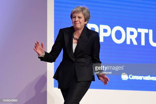 British Prime Minister Theresa May dances as she walks out onto the stage to deliver her leader's speech during the final day of the Conservative...