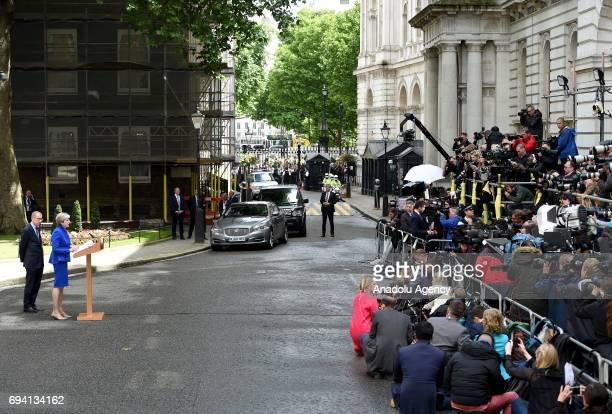 British Prime Minister Theresa May delivers a speech to members of the media as her husband Philip May watches outside number 10 Downing Street in...