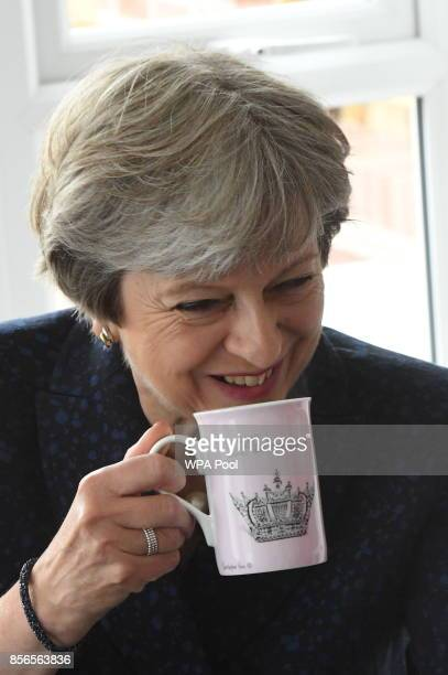 British Prime Minister Theresa May drinks from a mug that says 'Princess' s she visits Scholars Green housing development by Barratt homes in Walkden...