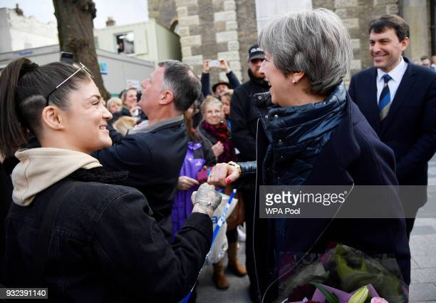 British Prime Minister Theresa May fist bumps a member of the public as she greets people after visiting the scene where former Russian intelligence...