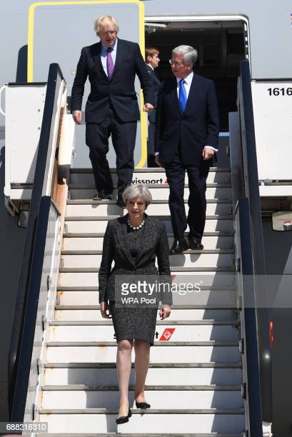 British Prime Minister Theresa May Foreign Secretary Boris Johnson and Defence Secretary Sir Michael Fallon disembark a plane as they arrive to...