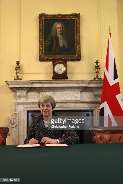 British Prime Minister Theresa May in the cabinet sitting below a painting of Britain's first Prime Minister Robert Walpole signs the official letter...