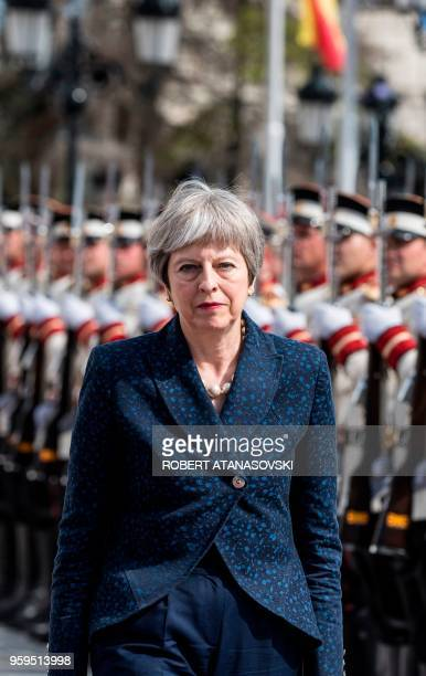 British Prime Minister Theresa May inspects a guard of honour during a welcome ceremony in front of the Government Building in Skopje on May 17 2018
