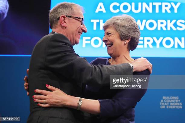 British Prime Minister Theresa May is embraced by husband Philip after delivering her keynote speech to delegates and party members on the last day...