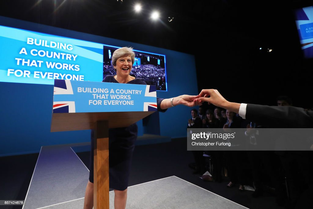British Prime Minister Theresa May is handed a cough sweet during her keynote speech to delegates and party members on the last day of the Conservative Party Conference at Manchester Central on October 4, 2017 in Manchester, England. The prime minister rallied members and called for the party to 'shape up' and 'go forward together'. Theresa May also announced a major programme to build council houses and a cap on energy prices.