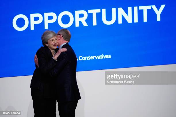 British Prime Minister Theresa May is joined on the stage by her husband Philip May after her leader's speech during the final day of the...
