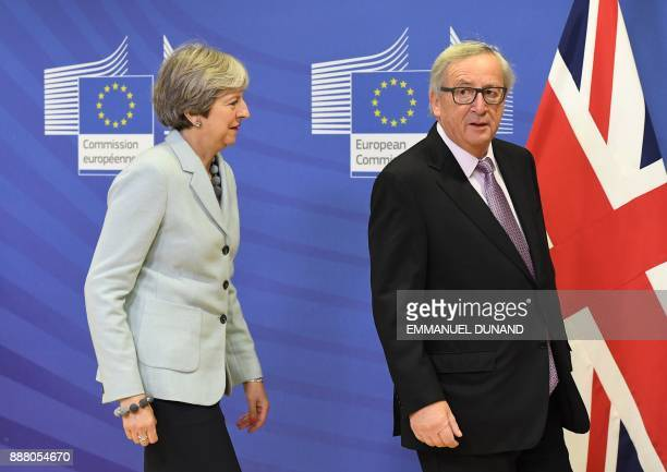 British Prime Minister Theresa May is welcomed by European Commission JeanClaude Juncker at European Commission in Brussels on December 8 2017 / AFP...