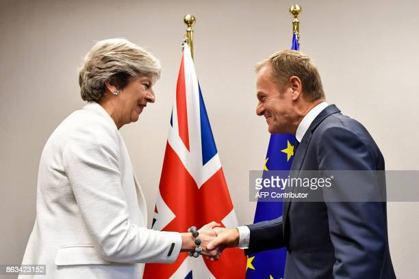 TOPSHOT British Prime Minister Theresa May is welcomed by European Council President Donald Tusk for a bilateral meeting during an EU summit in...