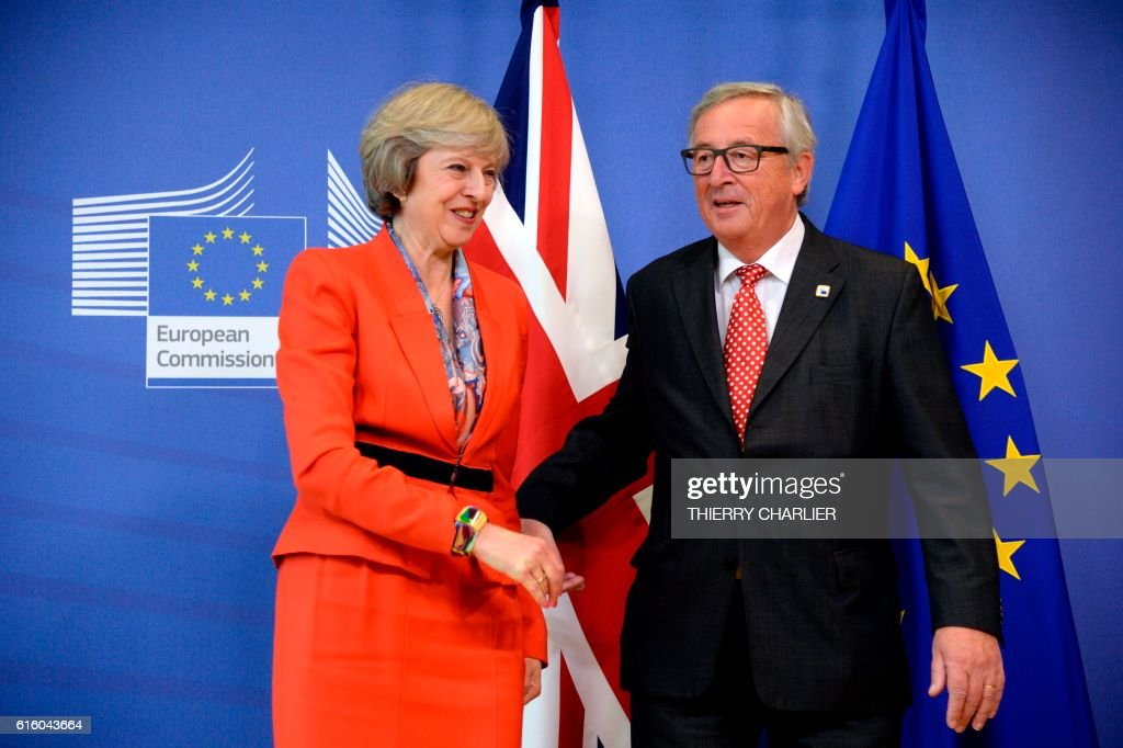 British Prime Minister Theresa May (L) is welcomed by European Union Commission President Jean-Claude Juncker before their meeting at the European Union Commission headquarter in Brussels, October 21, 2016. / AFP / THIERRY