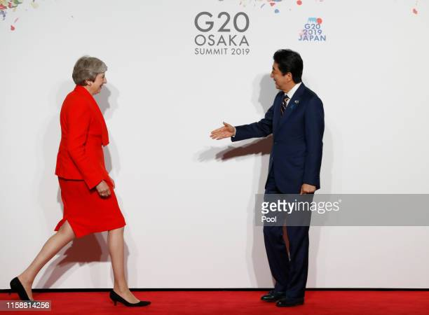 British Prime Minister Theresa May is welcomed by Japanese Prime Minister Shinzo Abe upon his arrival for a welcome and family photo session at G20...