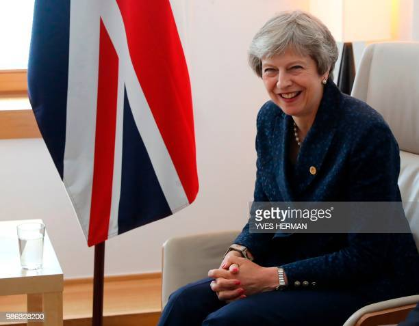 British Prime Minister Theresa May laughs during a bilateral meeting with Irish Prime minister during an European Union leaders' summit focused on...
