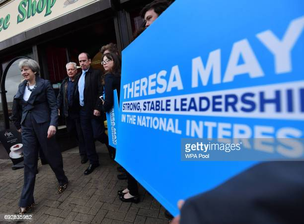 British Prime Minister Theresa May leaves a meeting with Conservative party supporters during an election campaign visit to a bakery during an...