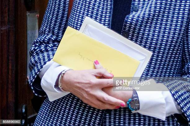 British Prime Minister Theresa May leaves holding a bundle of envelopes after attending the Sunday morning service at a church in her Maidenhead...