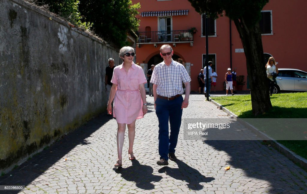 British Prime Minister Theresa May, left, walks with her husband Philip on July 25, 2017 in Desenzano del Garda, Italy. May is spending her holidays in northern Italy.