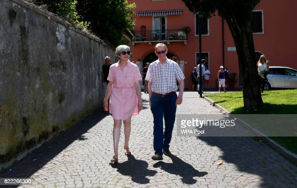 British Prime Minister Theresa May left walks with her husband Philip on July 25 2017 in Desenzano del Garda Italy May is spending her holidays in...