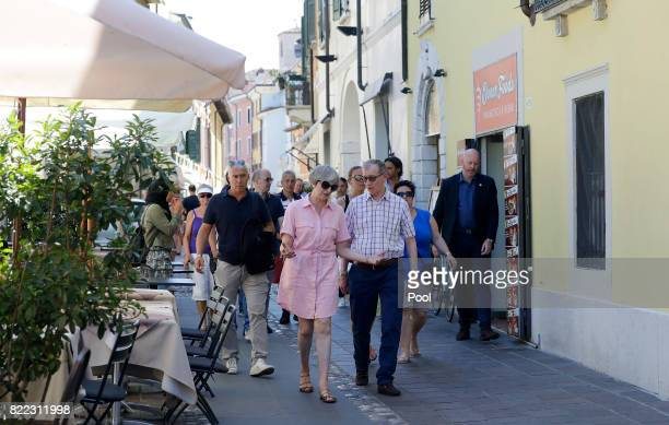 British Prime Minister Theresa May left walks with her husband Philip close to Lake Garda on July 25 2017 in Desenzano del Garda Italy May is...