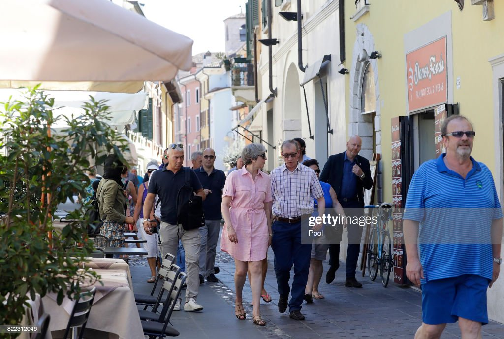 British Prime Minister Theresa May, left, walks with her husband Philip close to Lake Garda on July 25, 2017 in Desenzano del Garda, Italy. May is spending her holidays in northern Italy.