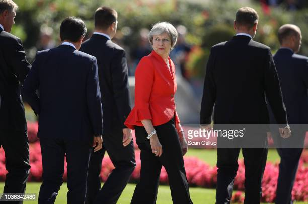 British Prime Minister Theresa May looks back as she and other leaders depart following the family photo on the second day of an informal summit of...