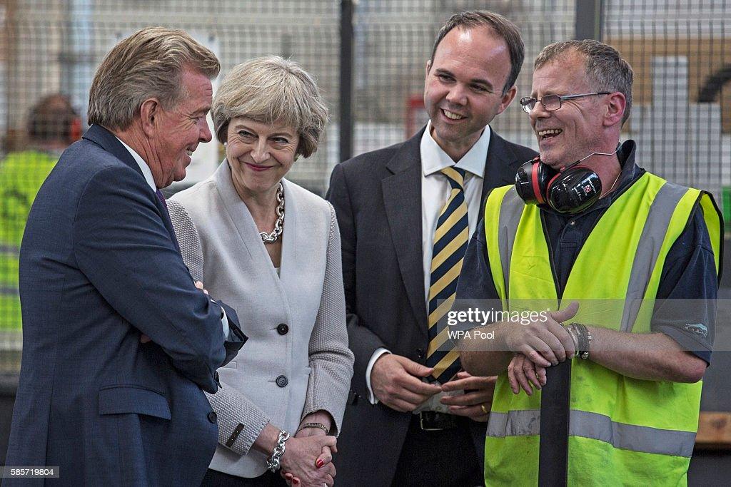 British Prime Minister Theresa May, Martek Managing Director Derek Galloway (L) and Croydon Central MP Gavin Barwell (2ndR) speak with a worker as they visit Martinek joinery factory on August 3, 2016 in London, United Kingdom.