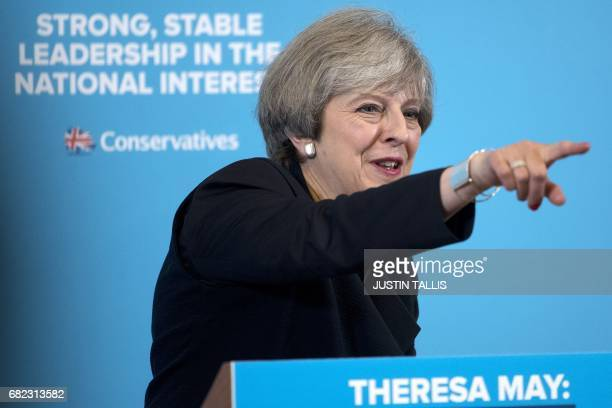 British Prime Minister Theresa May points to a member of the audience as she delivers a speech to an audience of supporters and members of the media...