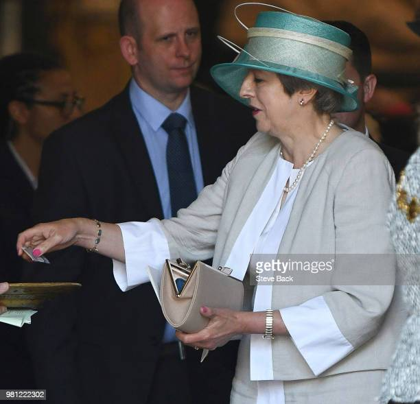 British Prime Minister Theresa May puts money into a collection plate as she leaves after attending the Service of Thanksgiving to mark the 70th...