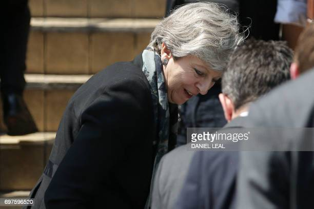 British Prime Minister Theresa May reacts as her shoe falls off whilst arriving at Finsbury Park Mosque in the Finsbury Park area of north London on...